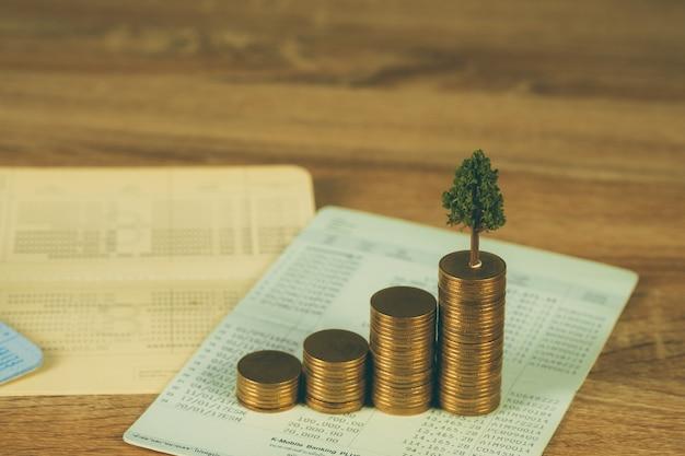 Arbre qui pousse sur des tas de pièces d'or et livre de comptes Photo Premium