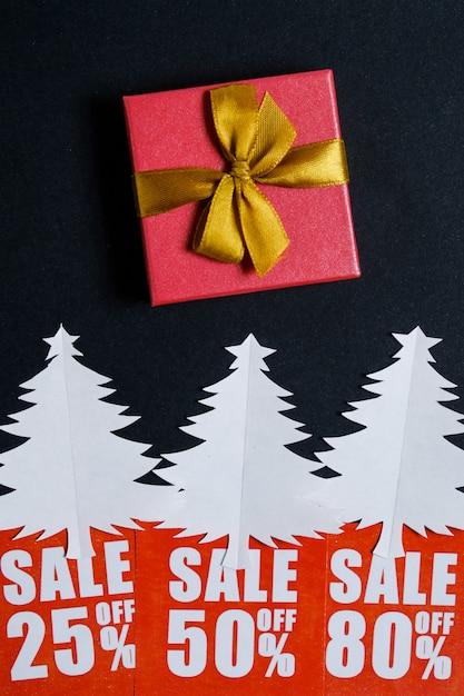 Arbres de noël en papier avec des cartes de réduction rouges et un cadeau Photo Premium