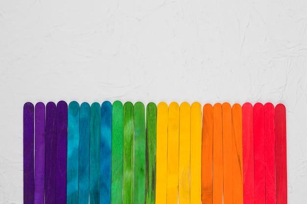Arc-en-ciel lgbt de bâtons de bois colorés sur une surface grise Photo gratuit