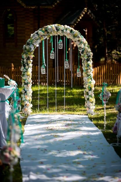 Arc pour la cérémonie de mariage. décoré avec des fleurs et de verdure. est situé dans une pinède. tout juste marié. décoration de mariage. Photo Premium