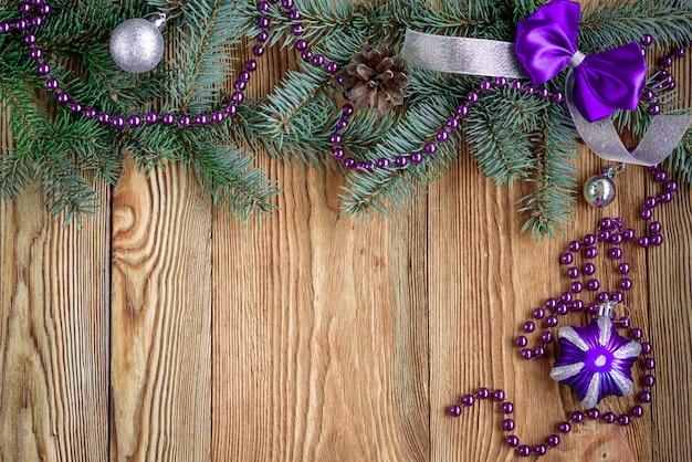 Arc Et Ruban Violet Décoratif. Composition De Noël Avec Des Branches De Sapin. Cônes, Perles Et Boules Sur Planche De Bois Avec Espace Copie. Photo Premium