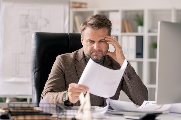 Architecte Ou Directeur Pensif Regardant Croquis Sur Papier Tout En Se Concentrant Sur Le Travail Par Bureau Au Bureau Photo Premium