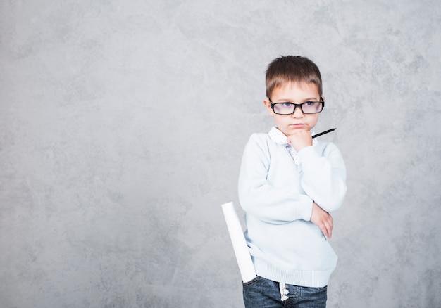 Architecte garçon réfléchie avec rouleau de papier dans la poche Photo gratuit