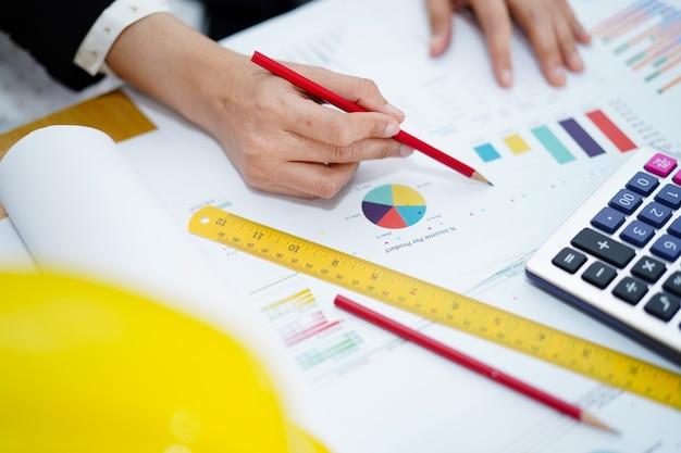 Architecte ou ingénieur travaillant la comptabilité de projet avec graphique. Photo Premium
