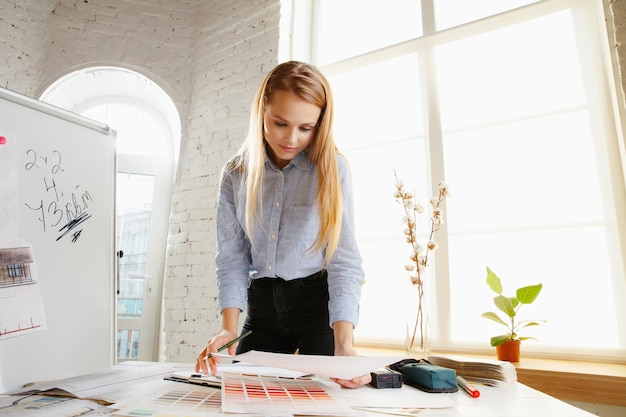 Architecte D'intérieur Professionnel Travaillant Avec Des Dessins De Salle Dans Un Bureau Moderne Photo gratuit