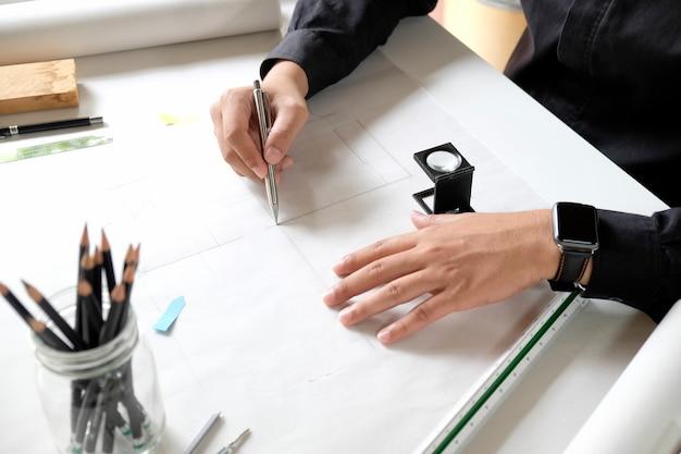 Architecte d'intérieur travaillant sur les plans au lieu de travail de studio de création. Photo Premium
