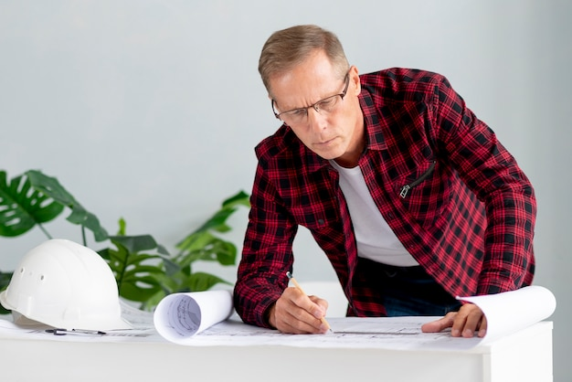 Architecte à lunettes travaillant sur projet Photo gratuit