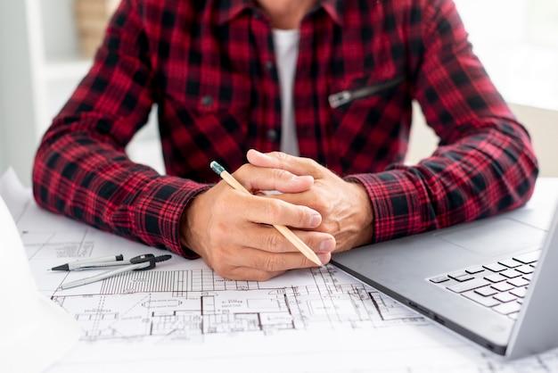Architecte avec des projets au bureau Photo gratuit