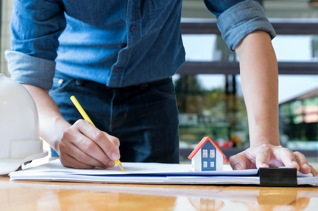 Architecte tenant un plan de maison de dessin au crayon jaune avec maison modèle sur le plan d'étage. Photo Premium