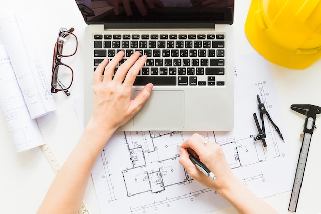 Architecte travaillant sur un projet de maison avec ordinateur portable Photo gratuit
