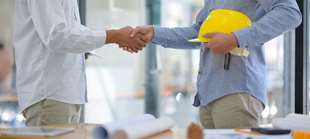 Les Architectes Et Les Entrepreneurs Se Serrent La Main Au Travail. Photo Premium
