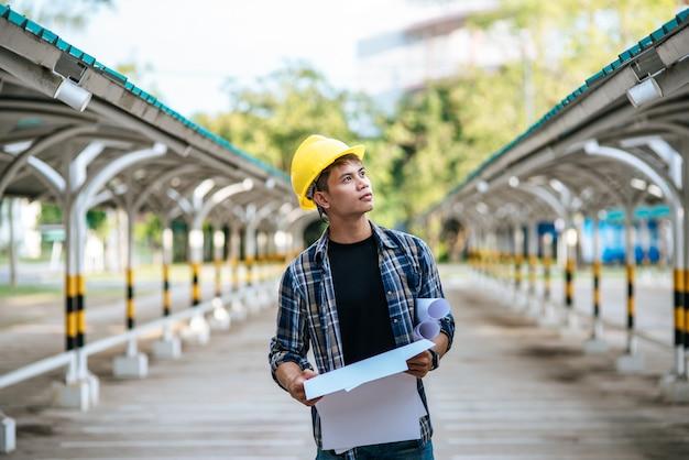 Les Architectes Tiennent Le Plan De Construction Et Vérifient Les Travaux. Photo gratuit