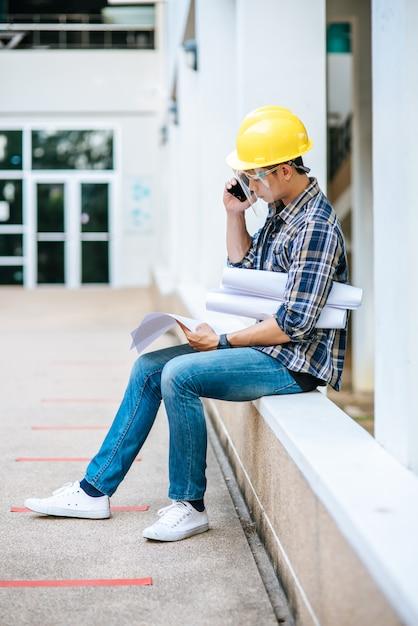 Les Architectes Tiennent Des Plans D'étage Et Parlent Au Téléphone. Photo gratuit