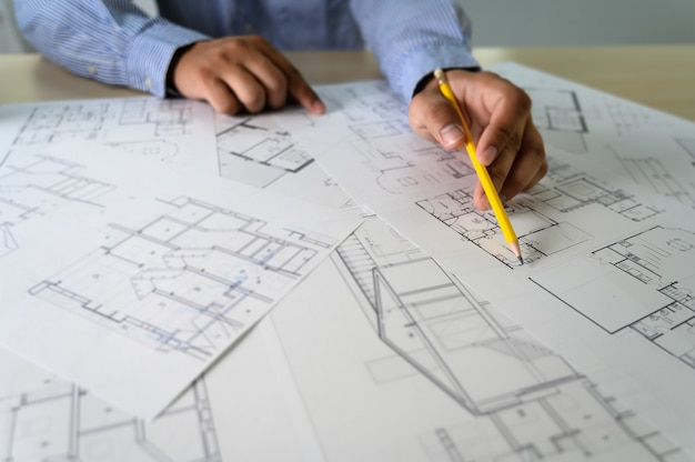Architectes travaillant sur un ordinateur portable à l'intérieur d'un lieu de travail d'architecte Photo Premium
