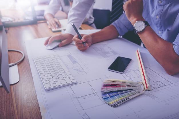 Architectures discutant du travail de données en dessinant un projet architectural sur un chantier de construction. Photo Premium