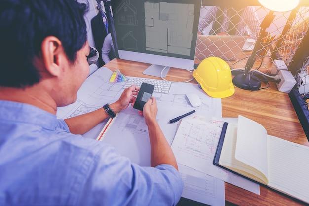 Architectures travaillant à dessiner sur un plan pour un projet architectural sur un chantier de construction Photo Premium