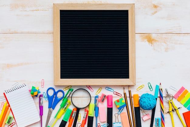 Ardoise avec des fournitures scolaires sur une table en bois Photo gratuit