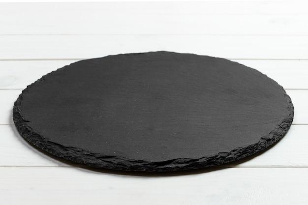 Ardoise noire ronde pierre sur fond en bois Photo Premium