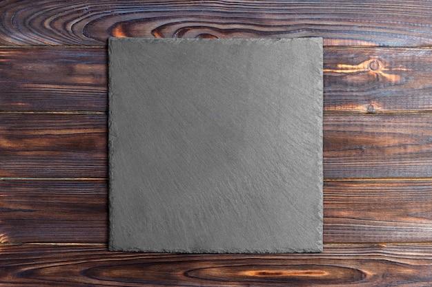 Ardoise tableau noir sur une table en bois sur fond en bois Photo Premium