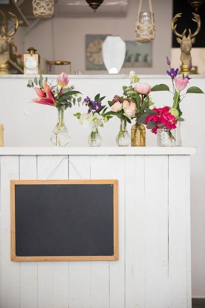Ardoise Vierge Accrochée Au Mur Avec De Beaux Vases à Fleurs Dans Le Magasin De Fleurs Photo gratuit