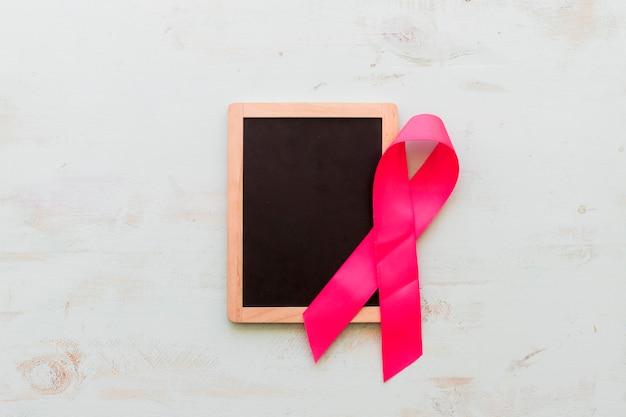 Ardoise vierge en bois avec ruban de sensibilisation rose sur un vieux fond Photo gratuit