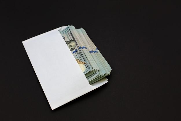 Argent dollar dans l'enveloppe sur fond noir Photo Premium