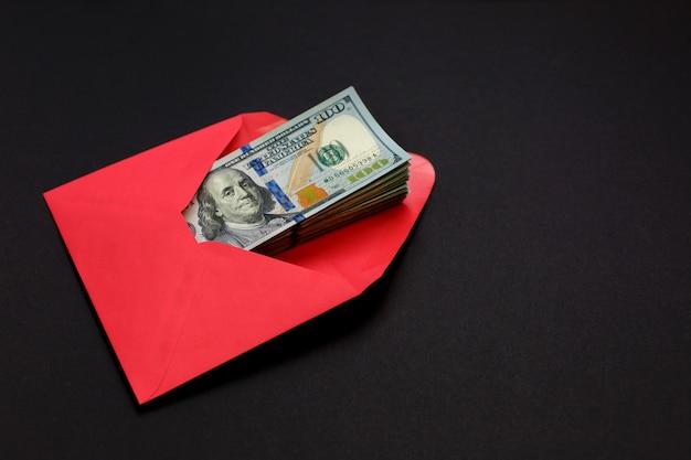 Argent dollar dans l'enveloppe rouge sur fond noir Photo Premium