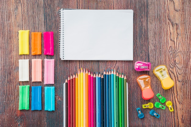Argile colorée et crayon avec bloc-notes en spirale blanche sur une table en bois Photo gratuit