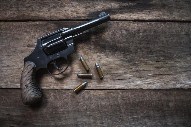 Arme à feu et munitions sur une table en bois. vue de dessus Photo Premium
