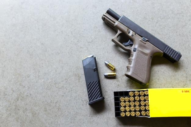 Arme de poing avec des munitions sur une table. pistolet et balle de 9 mm pour la défense. Photo Premium