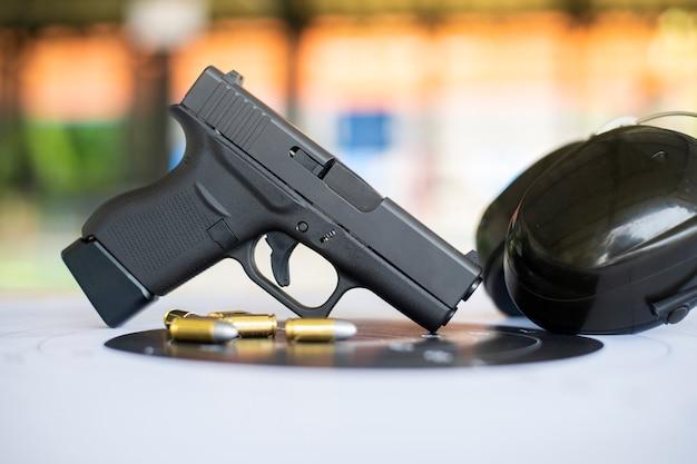 Armes à feu avec des munitions sur papier cible Photo Premium