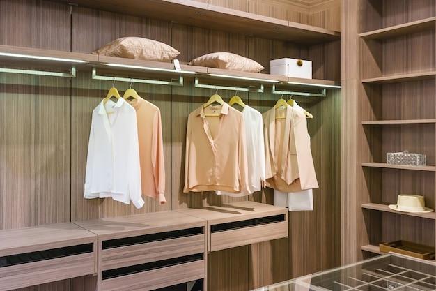 Armoire en bois moderne avec vêtements suspendus sur rail dans un intérieur design de placard Photo Premium