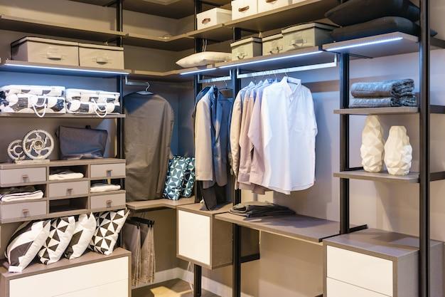 Armoire en bois moderne avec des vêtements suspendus sur rail dans walk in Photo Premium