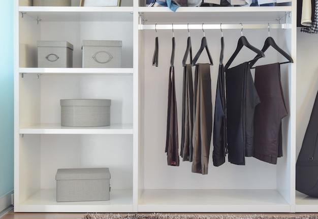 Armoire moderne avec rangée de pantalons suspendus dans une armoire blanche Photo Premium