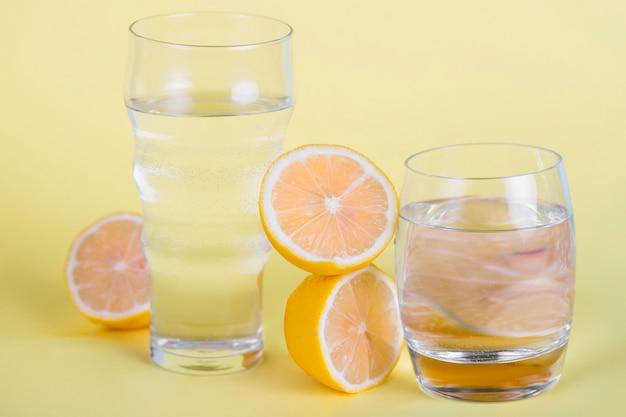 Arrangement avec des agrumes et des verres à eau Photo gratuit