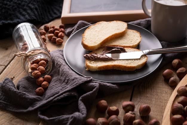 Arrangement à angle élevé avec du pain et des noisettes Photo gratuit