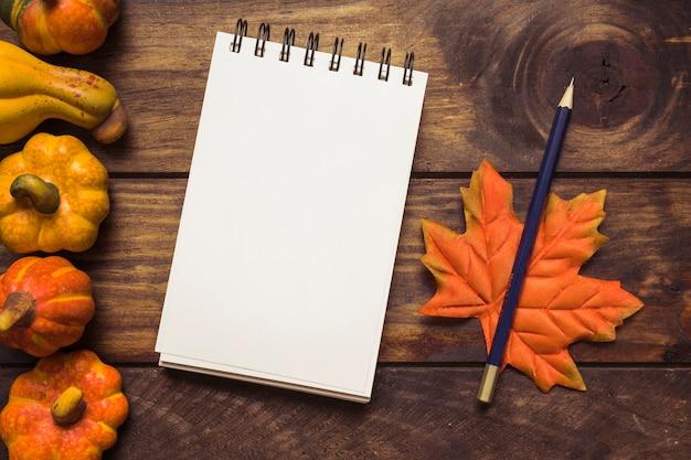 Arrangement d'automne avec le bloc-notes et les citrouilles Photo gratuit
