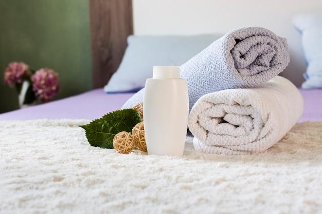 Arrangement avec une bouteille blanche et des serviettes sur le lit Photo gratuit