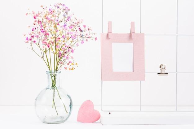 Arrangement avec cadre et vase à fleurs Photo gratuit