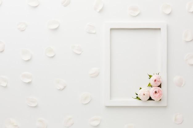 Arrangement De Cadre Vide Blanc Avec Roses Et Pétales Photo gratuit