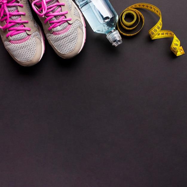 Arrangement avec des chaussures de course et une bouteille d'eau Photo gratuit