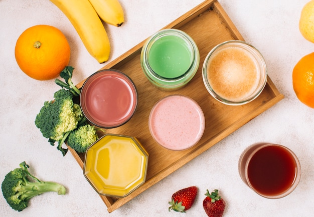 Arrangement coloré de smoothies et de fruits Photo gratuit