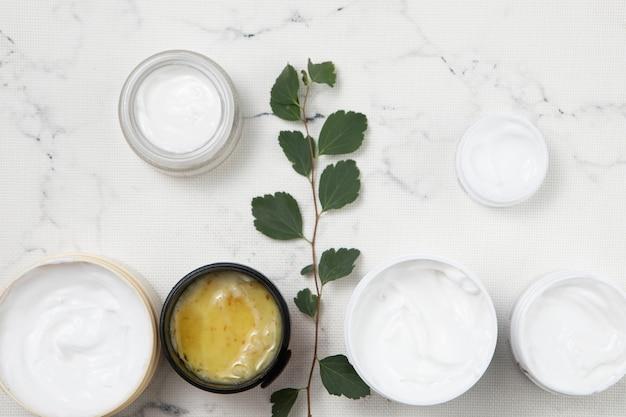 Arrangement de crème pour le corps plat sur fond de marbre Photo gratuit