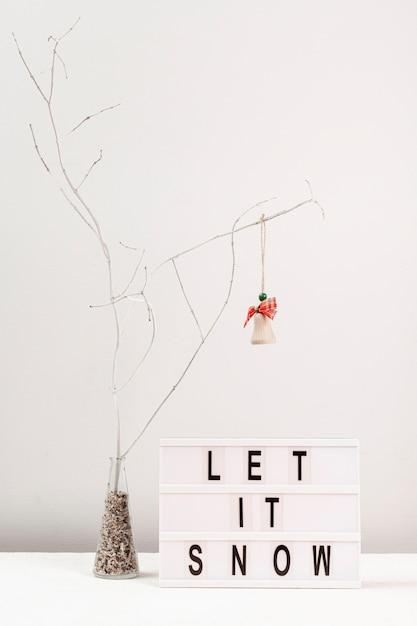 Arrangement avec décoration d'arbre et signe de neige Photo gratuit