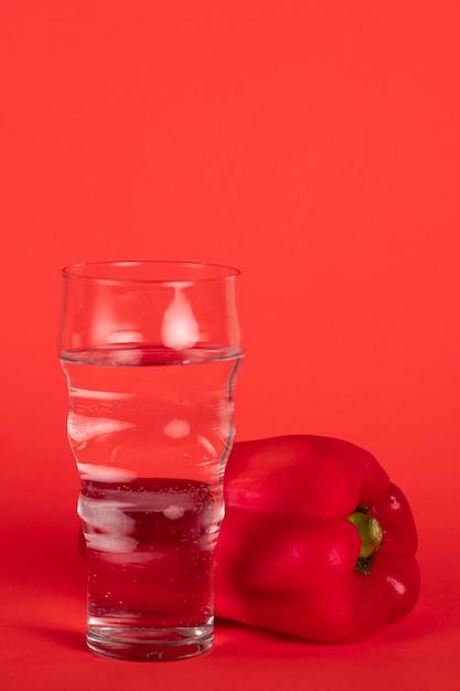 Arrangement avec du poivron rouge et un verre d'eau Photo gratuit
