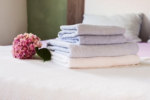 Arrangement avec fleur rose et serviettes sur le lit Photo gratuit