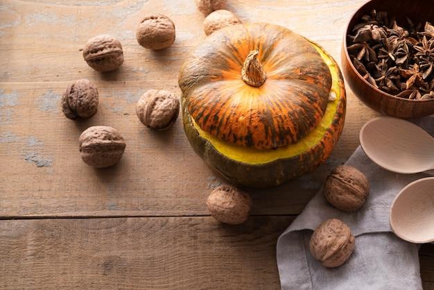 Arrangement grand angle avec citrouille et noix sur fond en bois Photo gratuit