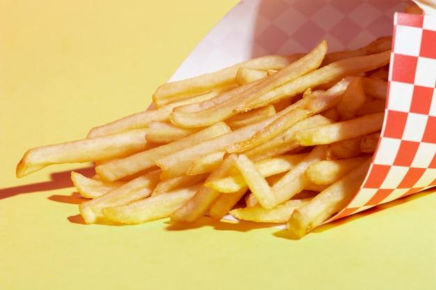 Arrangement grand angle avec frites et fond jaune Photo gratuit