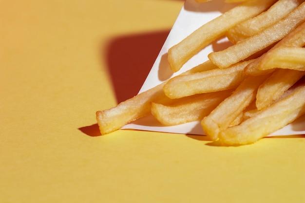 Arrangement grand angle avec des pommes de terre frites sur fond jaune Photo gratuit