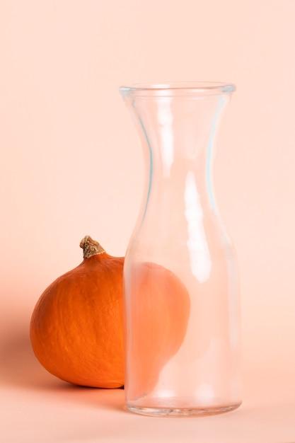 Arrangement avec grand verre vide et citrouille Photo gratuit
